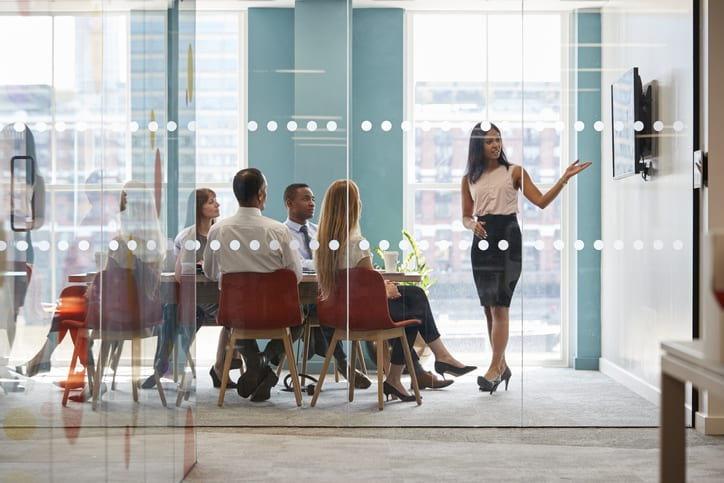 Female boss shows presentation on screen at business meeting